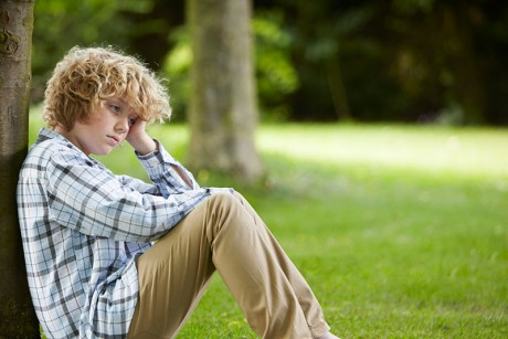A young person sitting leaning against a tree