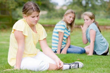 A young person sitting on grass feeling left out