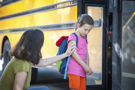 Parent sending reluctant child onto bus